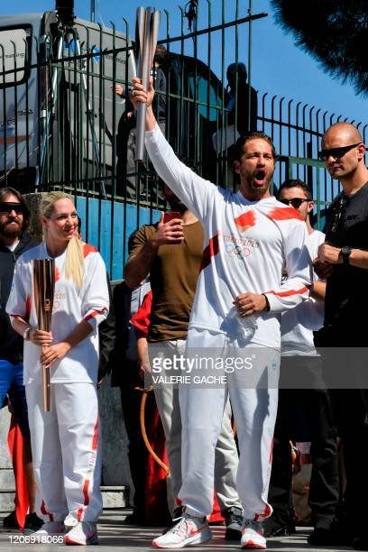 Actor Gerard Butler reacts as he holds the Olympic flame during the Olympic flame relay in Sparta on March 13, 2020 ahead of the Tokyo 2020 Olympic...
