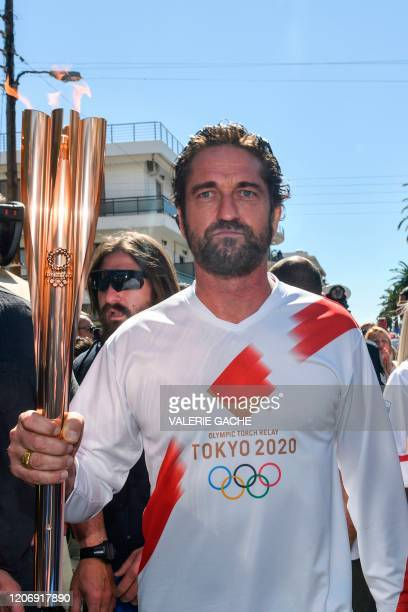 Actor Gerard Butler runs with the Olympic flame during the Olympic flame relay in Sparta on March 13, 2020 ahead of the Tokyo 2020 Olympic Games.