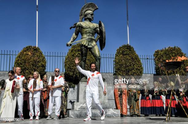 Actor Gerard Butler waves as he stands under a statue of the anciennt Spartan King Leonidas during the Olympic flame relay in Sparta on March 13,...