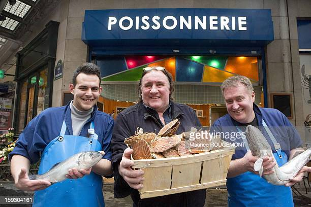 Actor Gerard Depardieu at his fishshop Moby Dick on January 4 2013 holding a box of scallop shells with his two fishmongers in Paris France