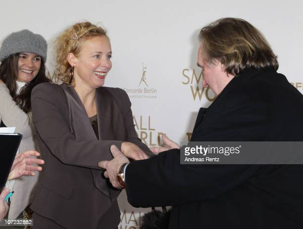 Actor Gerard Depardieu welcomes actress Katja Riemann at the 'Small World' premiere at Cinema Paris on December 1 2010 in Berlin Germany