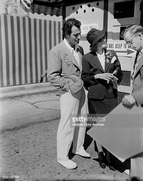 Actor Gilbert Roland and actress Constance Bennett talk to a fan in Los Angeles California