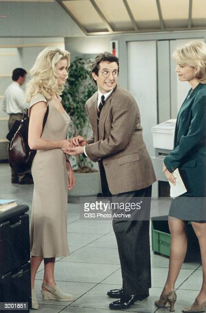 Actor Grant Shaud holds modelturnedactor Vendela Kirsebom's hand while looking over his shoulder and smiling at Faith Ford in a fulllength still from...