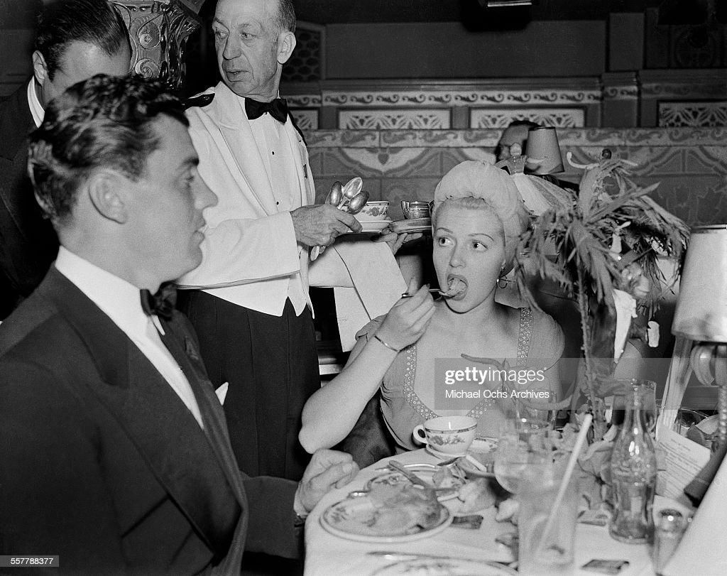 Actor Greg Bautzer and actress Lana Turner have dinner during an event in Los Angeles, California
