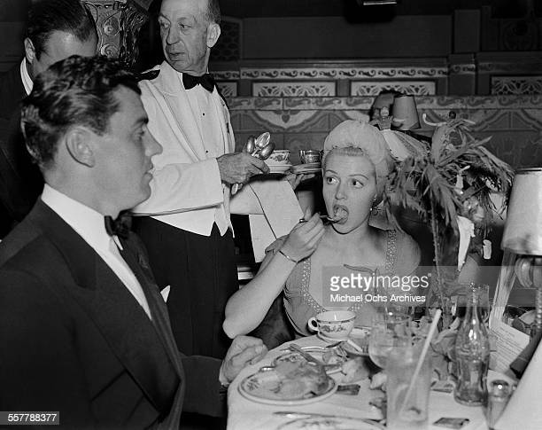 Actor Greg Bautzer and actress Lana Turner have dinner during an event in Los Angeles California