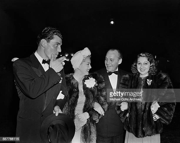 Actor Greg Bautzer and actress Lana Turner walk with Jack Benny and his wife Mary Livingston too an event in Los Angeles California