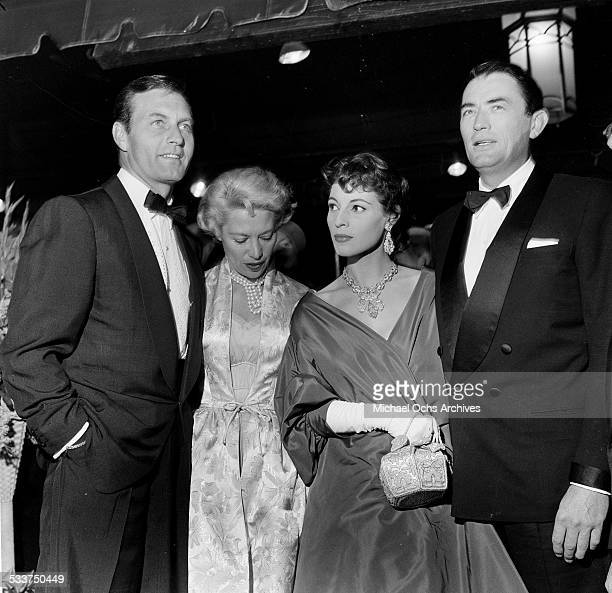 """Actor Gregory Peck and his wife Veronique Passani with actor George Montgomery and singer Dinah Shore attend the premiere of """"The Man in the Gray..."""