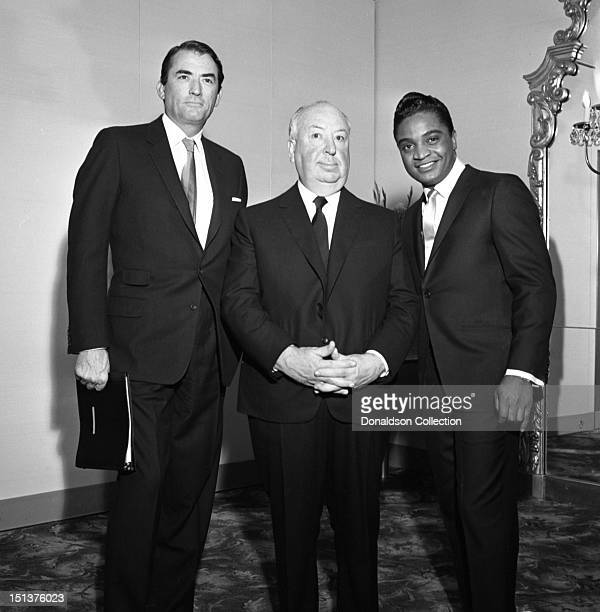 Actor Gregory Peck director Alfred Hitchcock and rock and roll singer Jackie Wilson pose for a portrait at a dinner for the Motion Picture Pioneers...