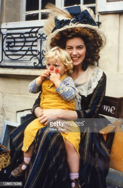 Actor Greta Scacchi takes a break from acting to sit with her daughter, during the filming of 'Jefferson in Paris' in Paris, in 1994.