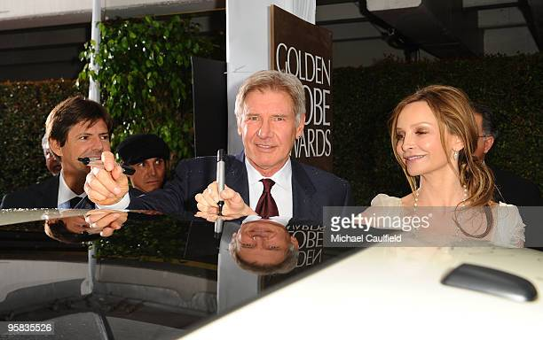 Actor Harrison Ford and actress Calista Flockhart sign the Chrysler 300 Eco Style car for Stars for a Cause during the 67th annual Golden Globe...
