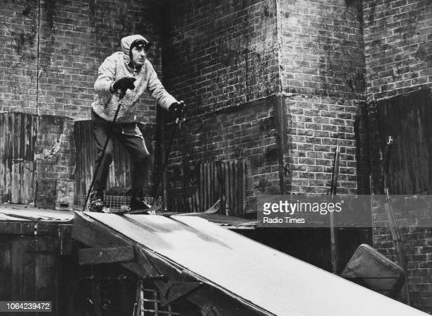 Actor Harry H Corbett wearing skiing clothing as he prepares to ski down a ramp in a scene from episode 'A Winter's Tale' of the television sitcom...