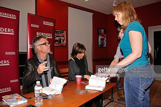 Actor Harry Hamlin signs an autograph for a fan as wife Lisa Rinna looks on at a signing event for their new books Full Frontal Nudity and Starlit on...