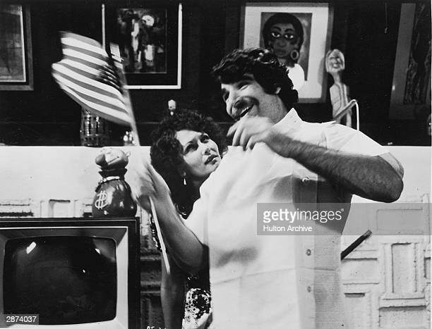 Actor Harry Reems waves an American flag as actor Linda Lovelace looks on in a still from the film 'Deep Throat' directed by Gerard Damiano 1972