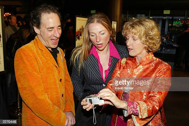 """Actor Harry Shearer , his wife Judith Owen and producer Karen Murphy look at pictures on a digital camera at the premiere of """"A Mighty Wind"""" at the..."""