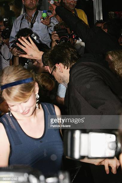 Actor Heath Ledger and Michelle Williams get soaked by photographers carrying water pistols during the red carpet walk at the Sydney premiere of...