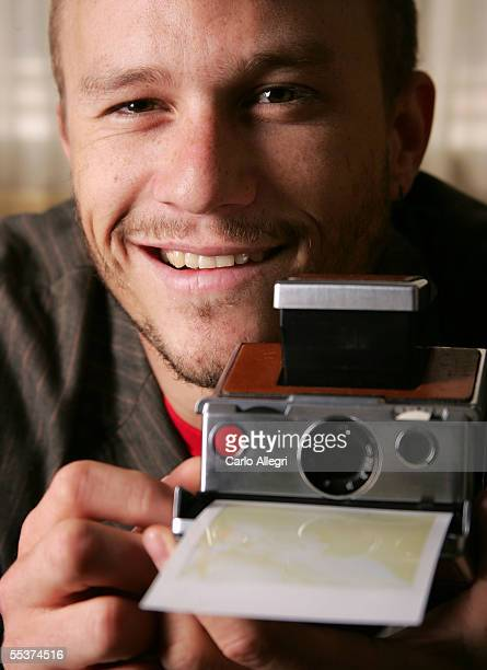 "Actor Heath Ledger poses for a portrait, holding a camera, while promoting his film ""Brokeback Mountain"" at the Toronto International Film Festival..."