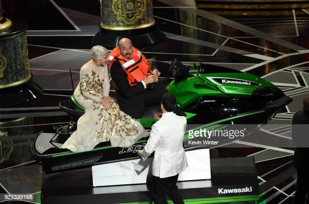 Actor Helen Mirren with Oscarwinning costume designer Mark Bridges sitting on a Jet Ski and host Jimmy Kimmel onstage during the 90th Annual Academy...
