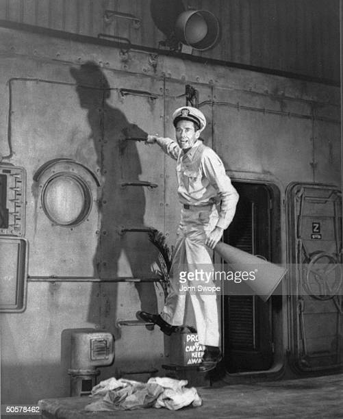 Actor Henry Fonda as Mr Roberts in play Mister Roberts hanging from ship's ladder