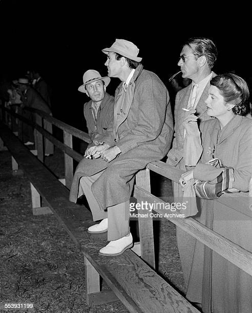 Actor Henry Fonda sits on a railing next to actor Gary Cooper and his wife actress Veronica Balfe during an event in Los Angeles California