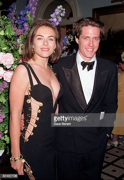 Actor Hugh Grant and actress Elizabeth Hurley, wearing a Gianni Versace dress, attend the premiere of 'Four Weddings and A Funeral' in Leicester...