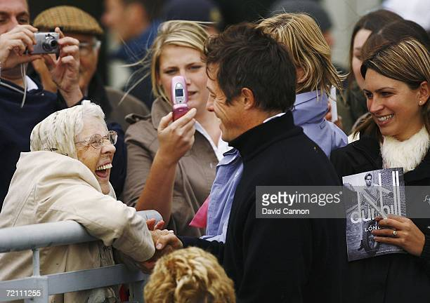 Actor Hugh Grant greets at fan at the 18th hole during the Third Round of The Alfred Dunhill Links Championship at Carnoustie Golf Club on October 7...