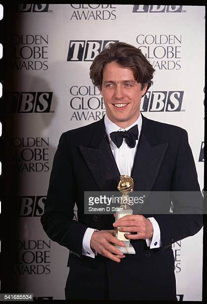 Actor Hugh Grant holds his Golden Globe Award for Best Actor in a Motion Picture Comedy for Four Weddings and a Funeral