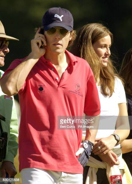 Actor Hugh Grant makes a phone call while standing with Roseanna InnesKerr the Duke of Roxburghe's daughter at the Roxburghe Challenge 2000 a...