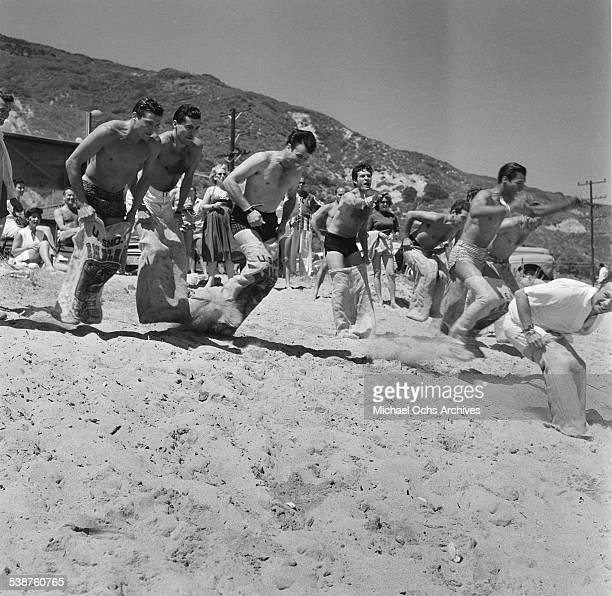 Actor Hugh O'Brian enters a sack race a during the Thalians Beach Ball in MalibuCalifornia