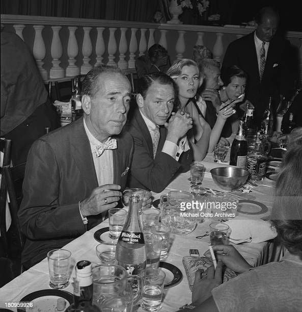 Actor Humphry Bogart dines with singer and actor Frank Sinatra actress Anita Ekberg and restaraunteur Mike Romanoff at Romanoff's Restaurant on...