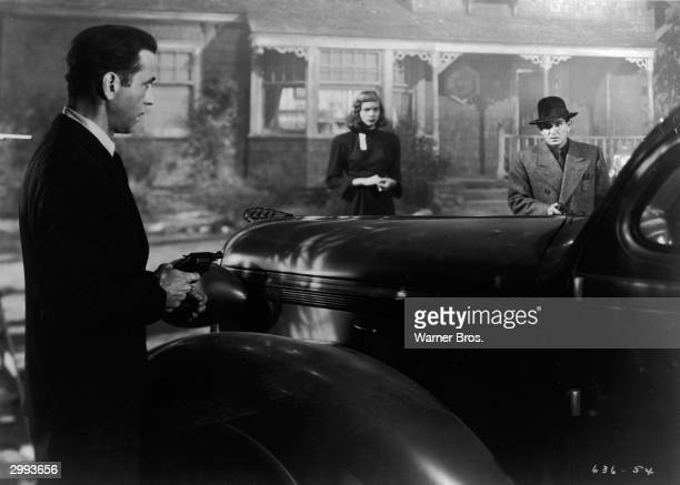 Actor Humphrey Bogart holds a pistol as Lauren Bacall and an unidentified actor look on in a still from the film 'The Big Sleep' directed by Howard...