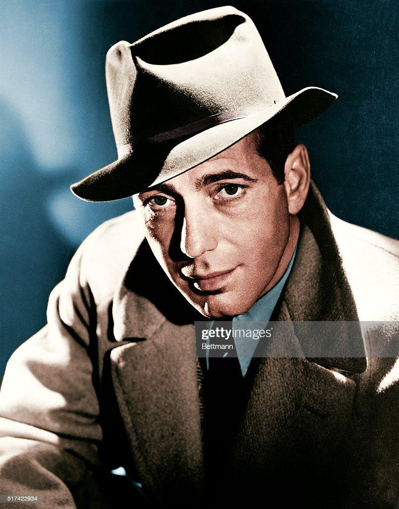 Actor Humphrey Bogart wearing a fedora hat and overcoat.