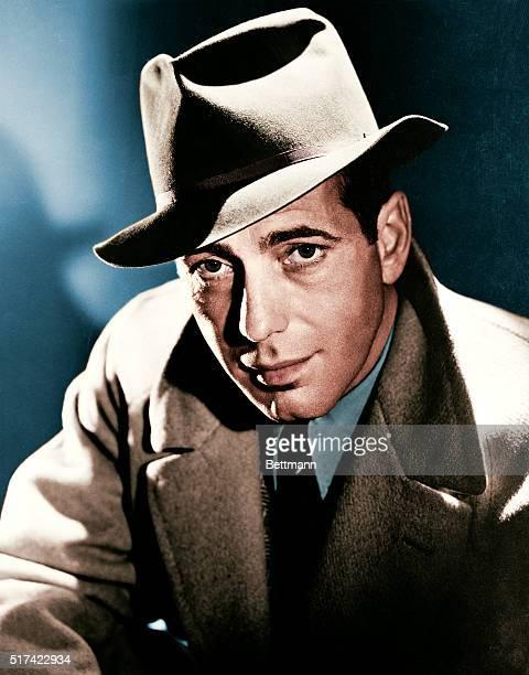 Actor Humphrey Bogart wearing a fedora hat and overcoat