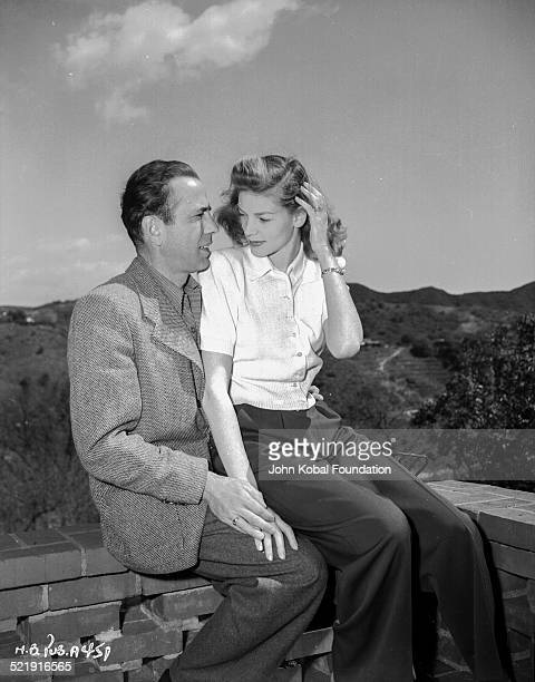 Actor Humphrey Bogart with his wife, actress Lauren Bacall , sitting together on a wall, for Warner Bros Studios, 1945.