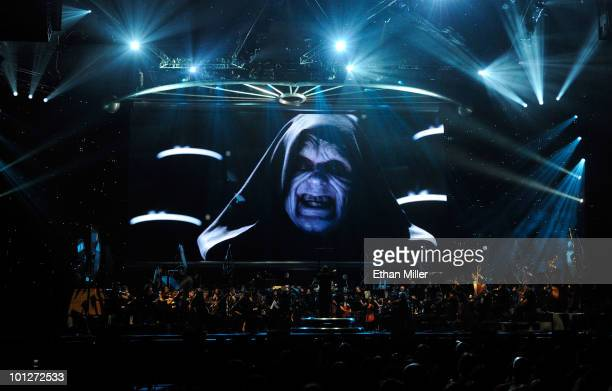 Actor Ian McDiarmid's Emperor Palpatine character from the Star Wars series of films is shown on screen while musicians perform during 'Star Wars In...