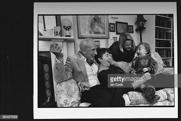 Actor Ian Richardson snuggling on couch w exactress wife Maroussa Frank who is singing w their granddaughter Annabel while holding her on her lap as...