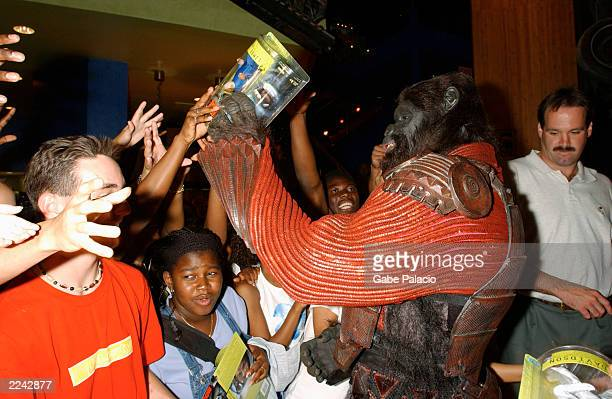Actor Isaac Singleton in Gorilla Warrior costume and makeup giving out Planet of the Apes action figures to fans after presenting an Apes Commander...