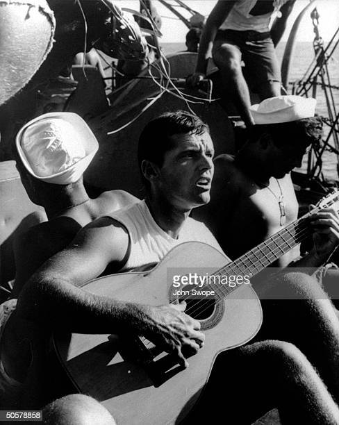 Actor Jack Nicholson strumming a guitar and singing during filming of Ensign Pulver