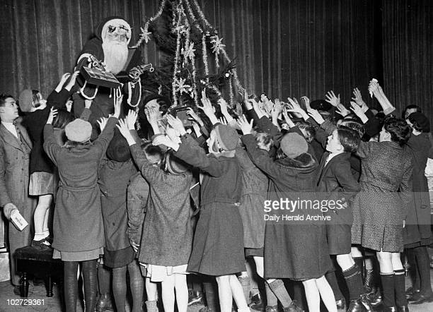 Actor Jack Payne as Father Christmas 7 December 1934 At a stage party at the Holborn Empire in London Father Christmas handedout presents to some of...
