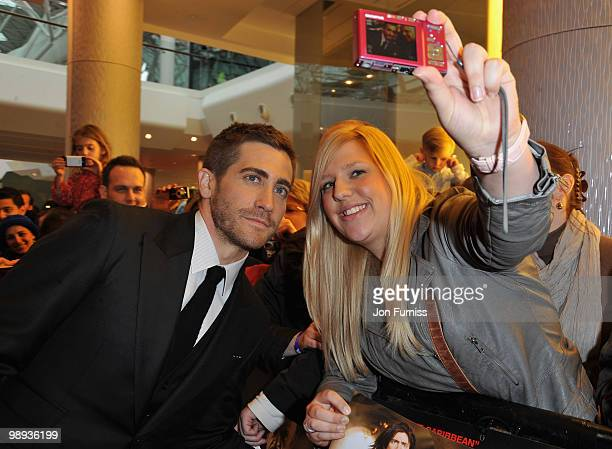 Actor Jake Gyllenhaal poses with a fan as he attends the 'Prince Of Persia: The Sands Of Time' world premiere at the Vue Westfield on May 9, 2010 in...