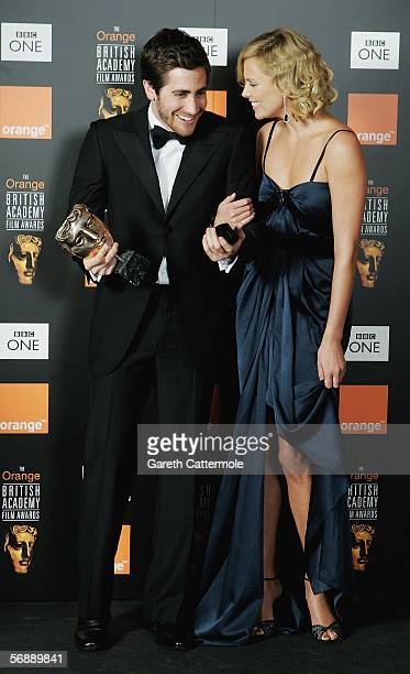 Actor Jake Gyllenhaal winner of Actor in a Supporting Role for 'Brokeback Mountain' and presenter Charlize Theron pose backstage in the Awards Room...
