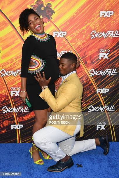 """Actor Jamal Mallory-McCree kneels to kiss the pregnant belly of US actress Angela Lewis as they arrive for FX's """"Snowfall"""" season 3 premiere..."""