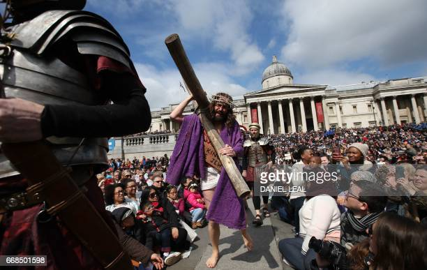 Actor James BurkeDunsmore playing the role of Jesus Christ carries the cross during a performance of Wintershall's 'The Passion of Jesus' on Good...