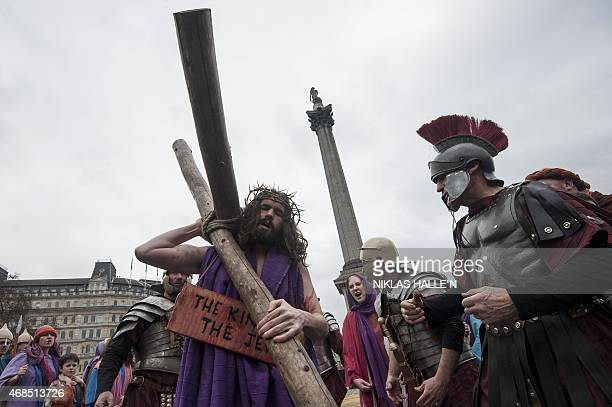 Actor James BurkeDunsmore plays the role of Jesus Christ carries a cross for his 'crucifixion' during a performance of Wintershall's 'The Passion of...