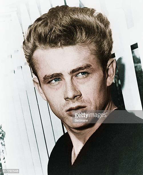 Actor James Dean leaning against a picket fence