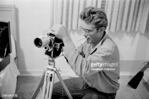 Actor James Dean sets up his camera in his hotel room during the filming of the movie Giant in October 1955 in Marfa Texas