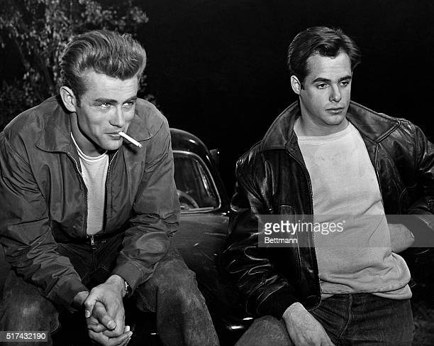 Actor James Dean smokes a cigarette beside another actor in a scene from Rebel Without a Cause