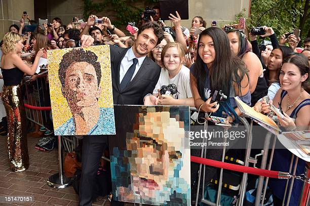 Actor James Franco poses with fans and portraits of himself as he attends the Spring Breakers premiere during the 2012 Toronto International Film...
