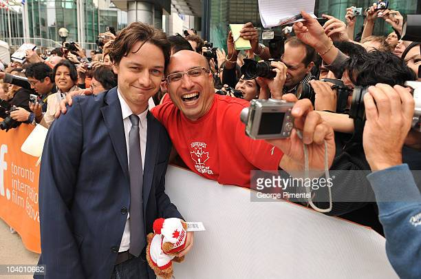 Actor James McAvoy poses for a photo with a fan as he arrives at 'The Conspirator' Premiere held at Roy Thomson Hall during the 35th Toronto...