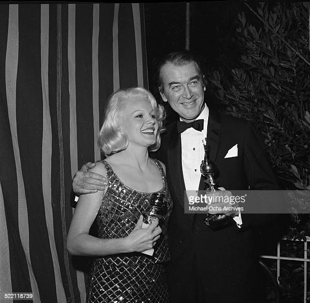 Actor James Stewart poses with Carol Baker and his Cecil B DeMille Award Lifetime Achievement Award during the Golden Globes in Los AngelesCA