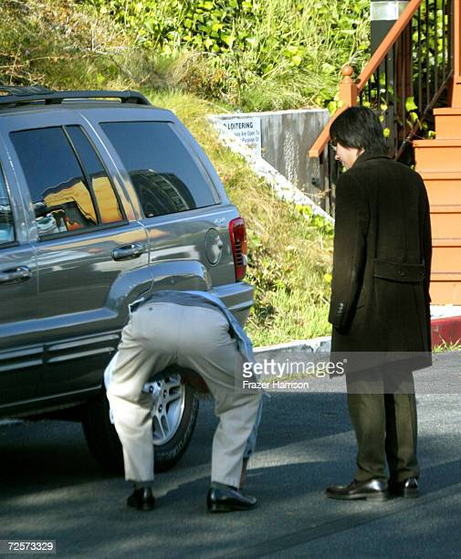 Actor James Woods checks his tires as his friend looks on outside Cafe Med restaurant February 19 2002 in Los Angeles CA